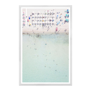 White sand and pastel aqua waters beckon in this aerial photo of a sunny and obviously hot coastal scene. Bright touches of pink and blues accent the atmosphere ...such fun. Framed in a clean, white, deep profile. Outside Dimensions: 37.5 in x 57.5 inArtist: Celement Designs
