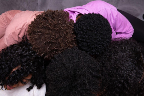 A group of canvas girls putting their afros together showing different curl patterns