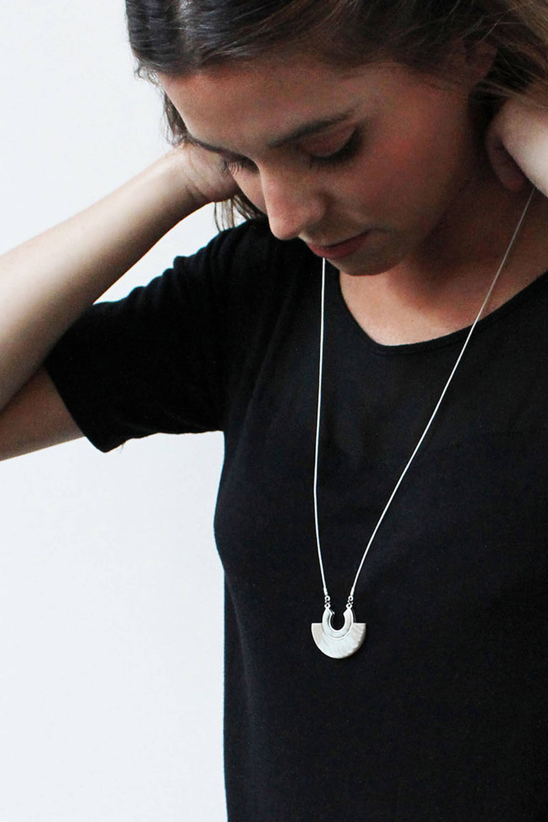model wearing Aurore beige resin and hypoallergenic stainless steel necklace handmade in Montreal Canada