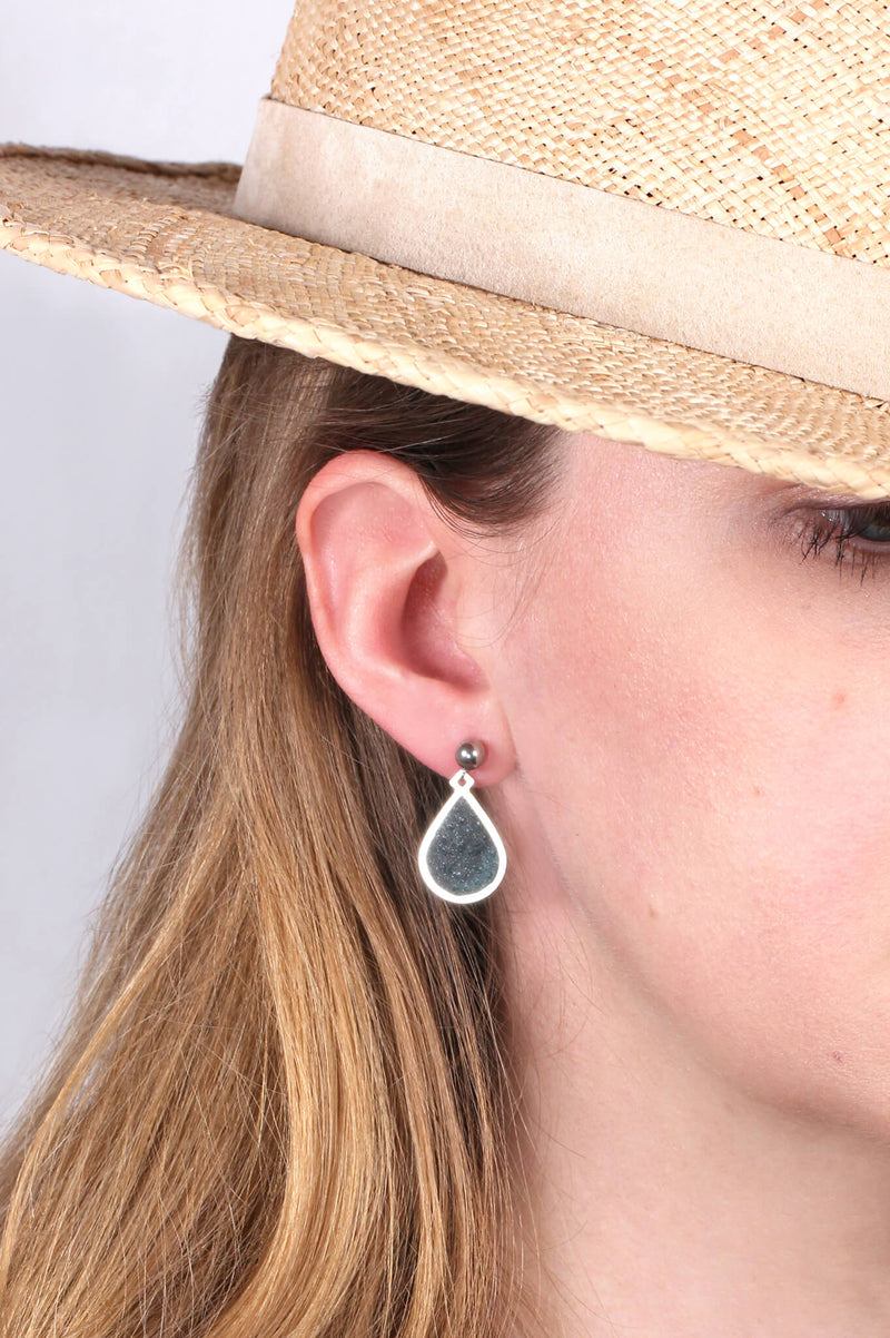 model wearing Candide teardrop studs in forest green resin and hypoallergenic stainless steel