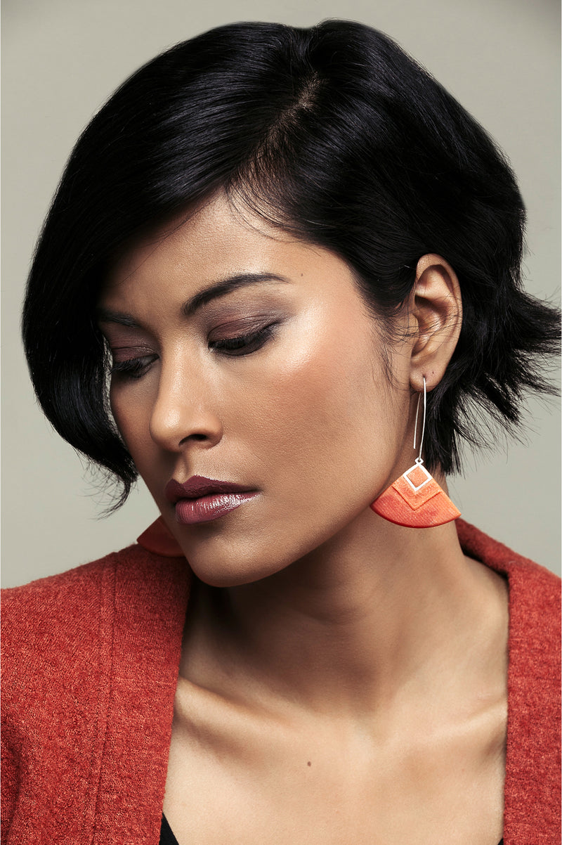 dark-haired model wearing Cléopâtre statement earrings, in coral red resin and hypoallergenic stainless steel