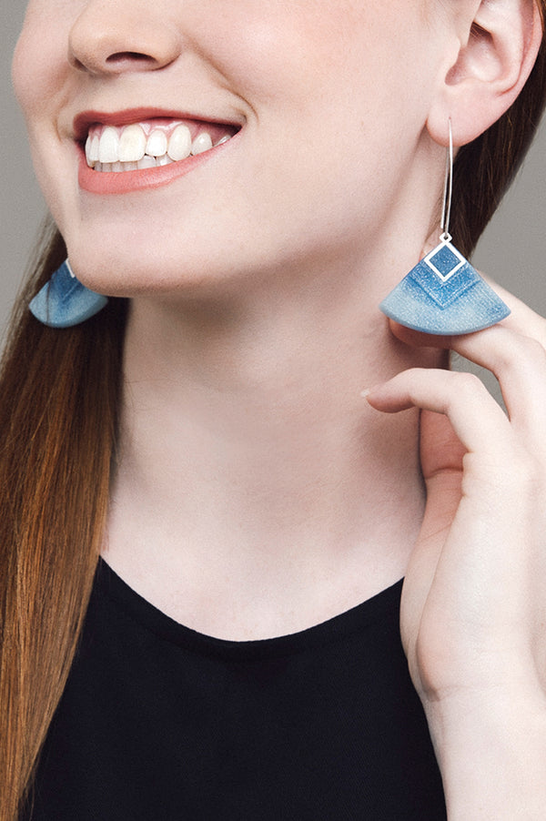 model wearing Cléopâtre statement earrings, in marbled indigo and pastel blue resin and hypoallergenic stainless steel