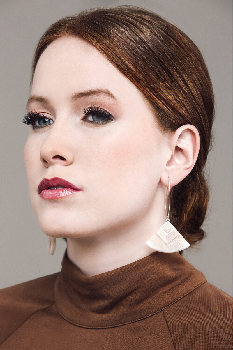 redhead model wearing Cléopâtre statement earrings, in beige resin and hypoallergenic stainless steel