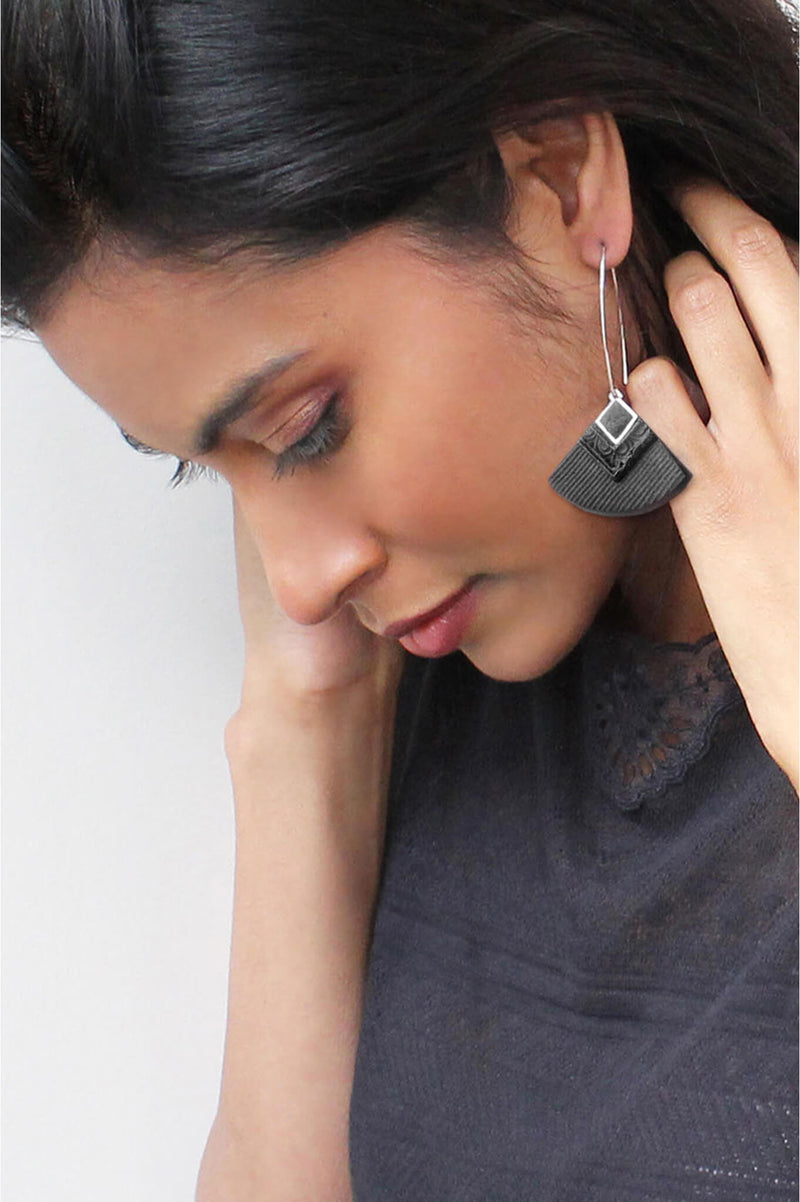 dark-haired model wearing Cléopâtre statement earrings, in black resin and hypoallergenic stainless steel