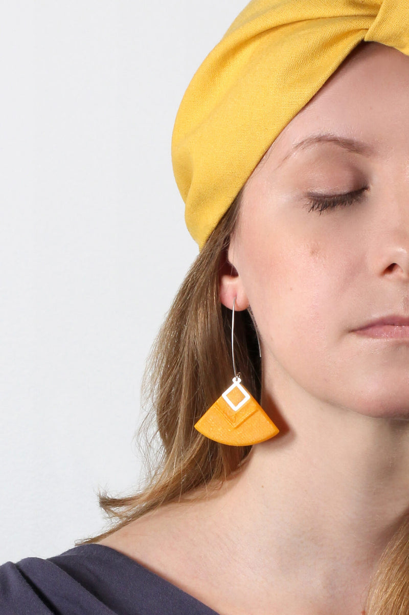 blonde model wearing Cléopâtre statement earrings, in golden-yellow resin and hypoallergenic stainless steel