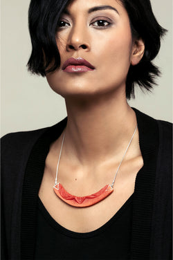 dark-haired model wearing Couronne, handmade necklace in coral red resin and hypoallergenic stainless steel