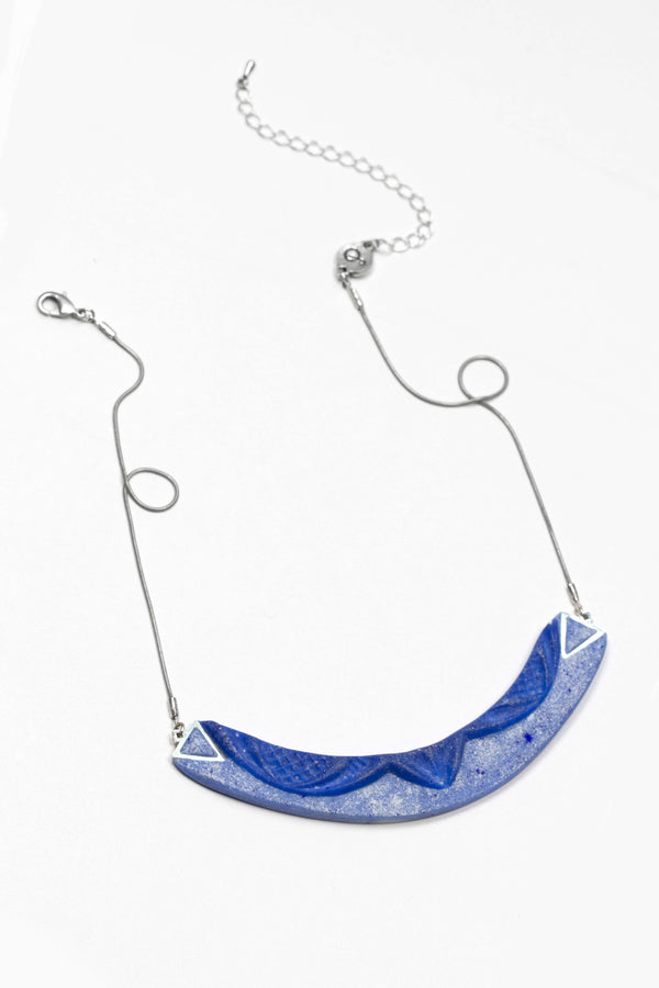 dark-haired model wearing Couronne, handmade necklace in indigo blue resin and hypoallergenic stainless steel