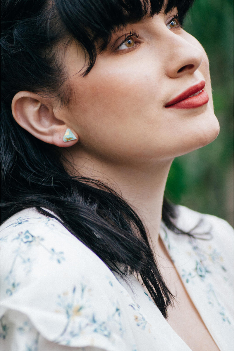model wearing Montreal designer Bijoux Pépine's white resin and gold leaf Diamant earrings