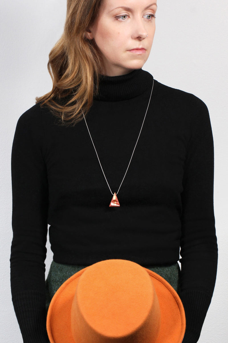 female model wearing Eclat, triangular pendant necklace in coral red resin and gold leaf