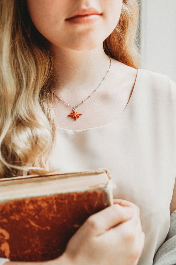 fashion model wearing Etoile du Berger, handmade star-shaped necklace in coral red resin and hypoallergenic stainless steel