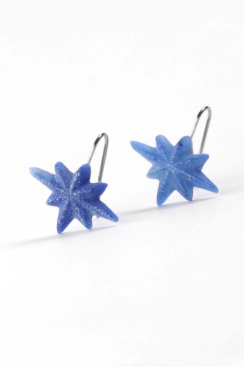fashion model wearing Etoile du Berger, handmade star-shaped earrings in blue indigo resin and hypoallergenic stainless steel