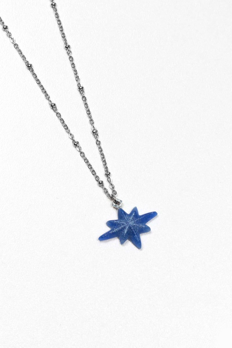 fashion model wearing Etoile du Berger, handmade star-shaped necklace in blue indigo resin and hypoallergenic stainless steel