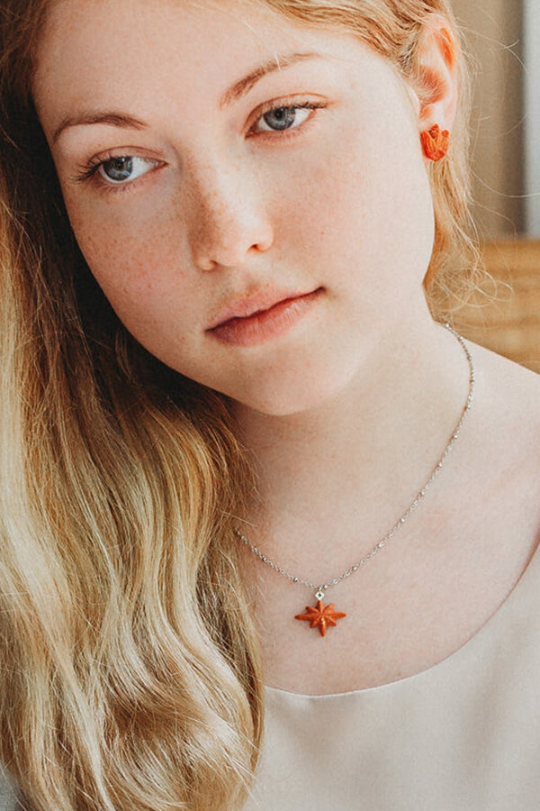 fashion model wearing matching coral red Lys studs and Etoile du Berger necklace