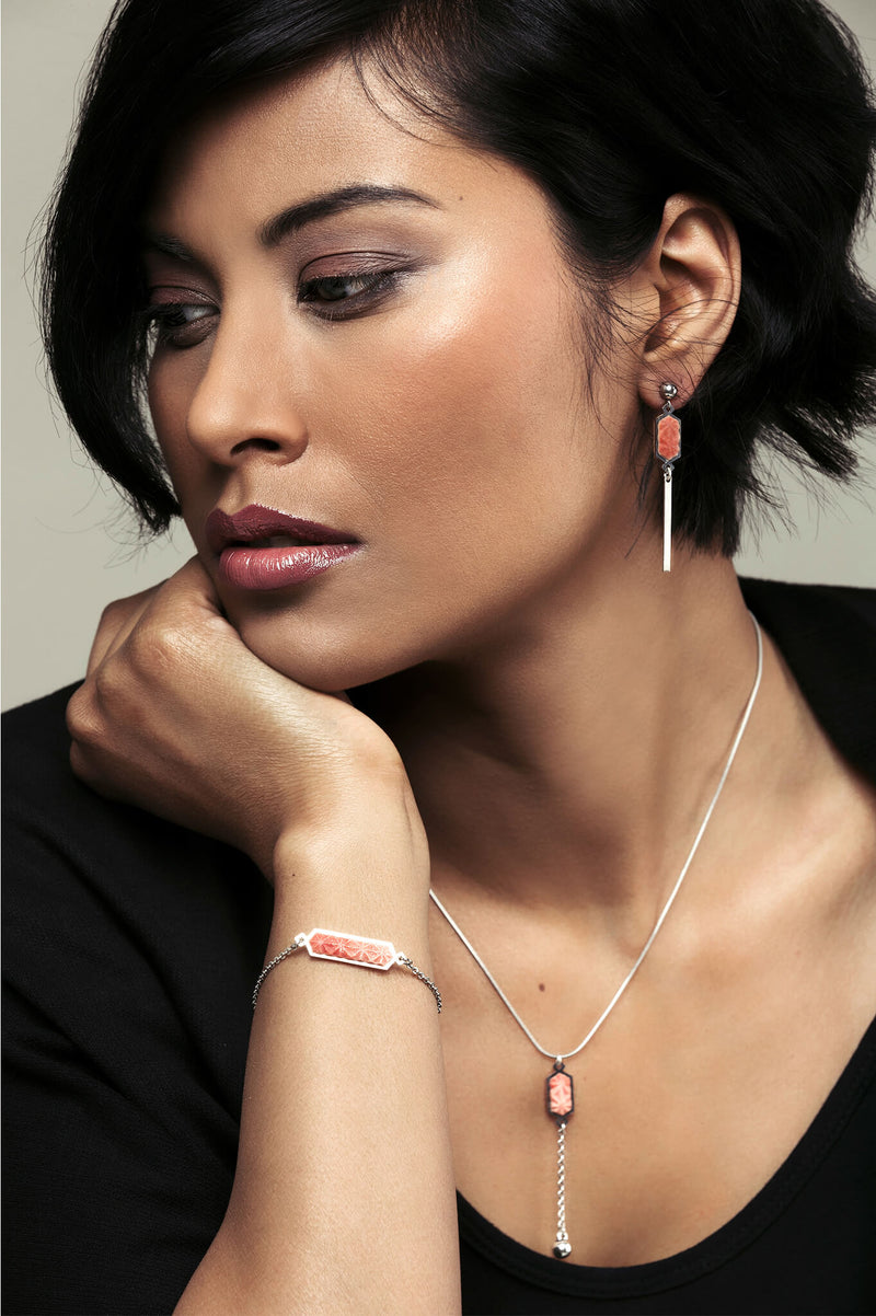 model wearing Bijoux Pépine's handmade Nova stud earrings in coral red