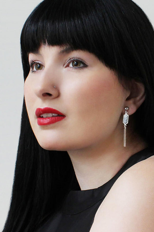 black-haired model wearing Bijoux Pépine's handmade Nova stud earrings in grey
