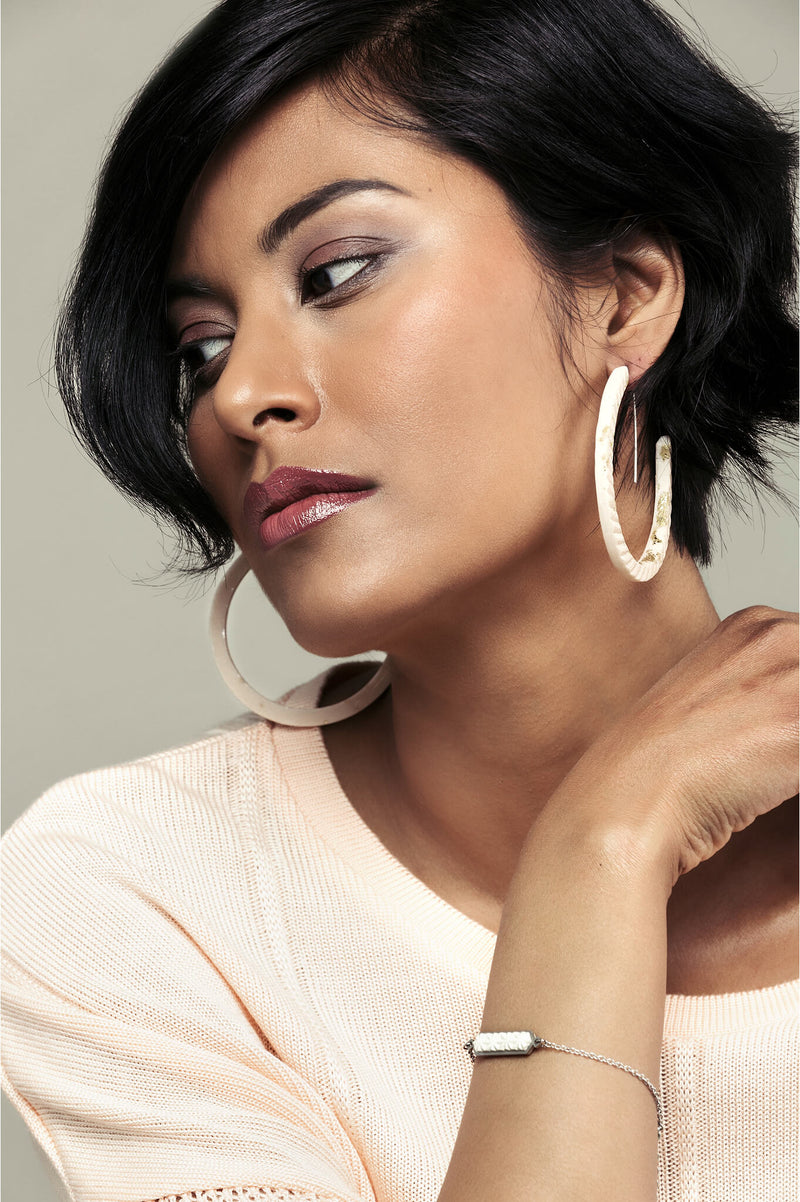 fashion model wearing Bijoux Pépine's handmade Ouroboros hoops in beige