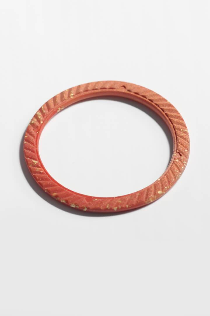 Ouroboros, Bijoux Pépine's handmade bangle bracelet in coral red resin and 24 karat gold leaf