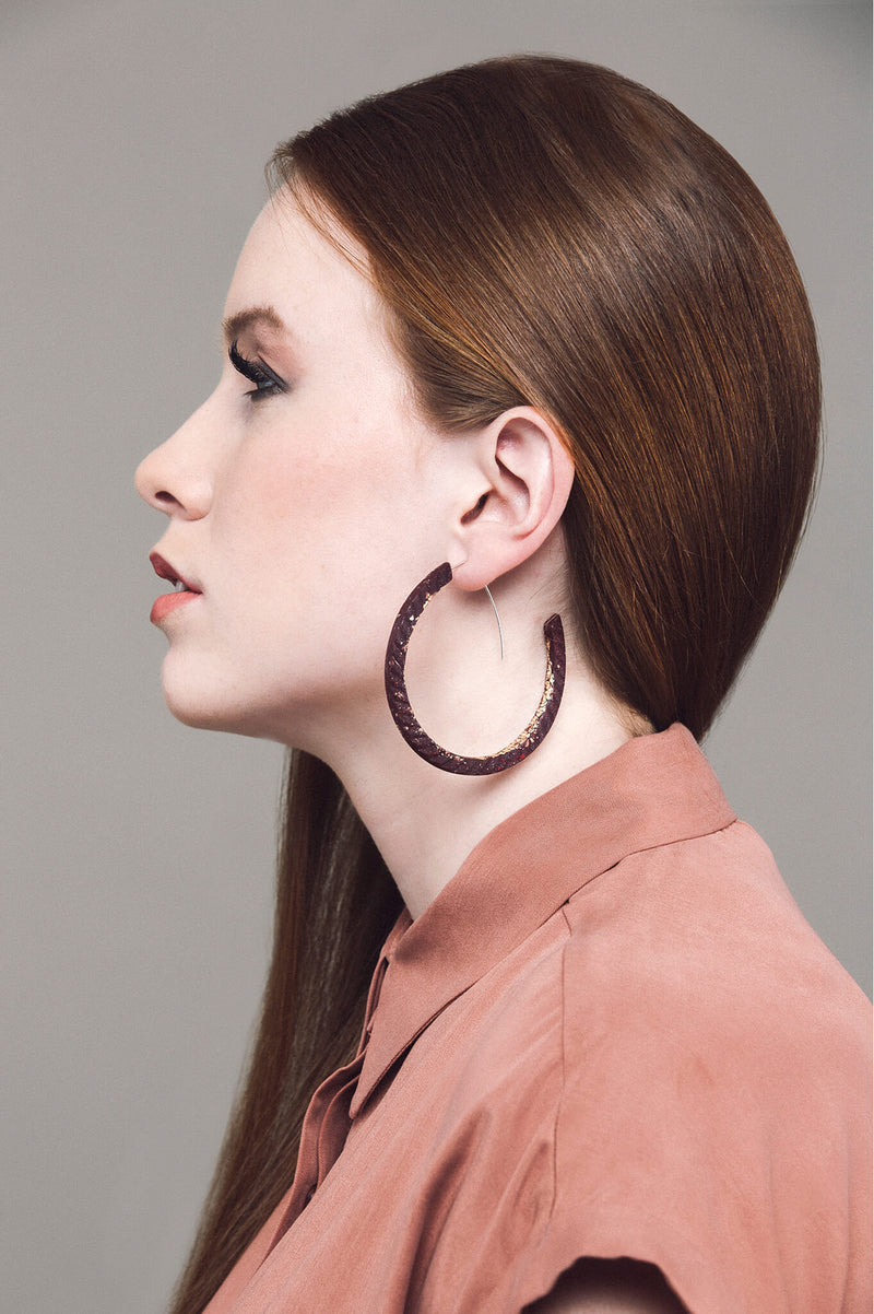 redhead model wearing Bijoux Pépine's handmade Ouroboros hoops in burgundy red