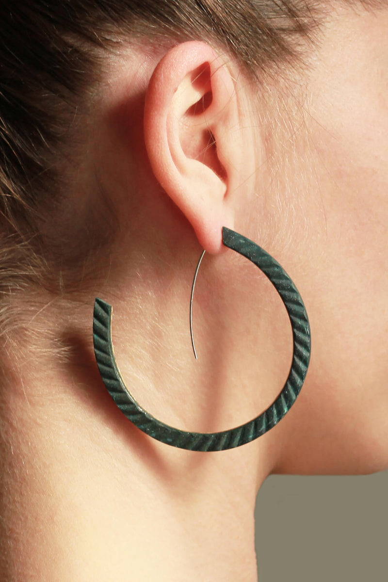 fashion model wearing Bijoux Pépine's handmade Ouroboros hoops in forest green