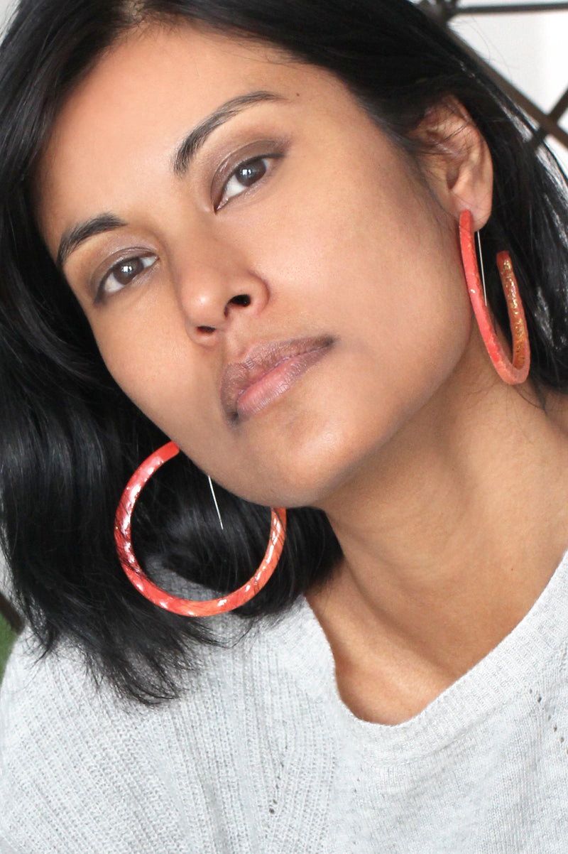 fashion model wearing Bijoux Pépine's handmade Ouroboros hoops in coral red