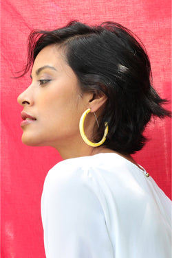 dark-haired model wearing Bijoux Pépine's handmade Ouroboros hoops in golden ochre yellow