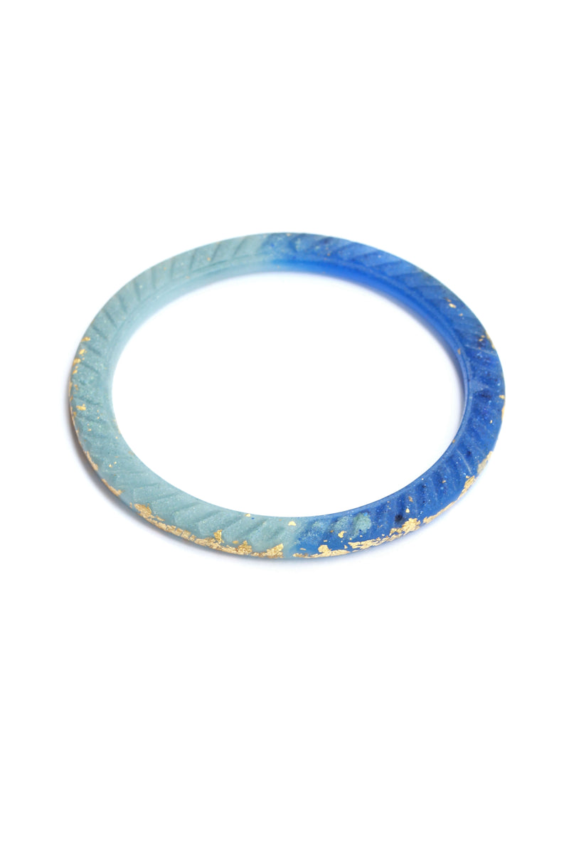 Ouroboros, Bijoux Pépine's handmade bangle bracelet in translucent blue indigo resin and 24 karat gold leaf