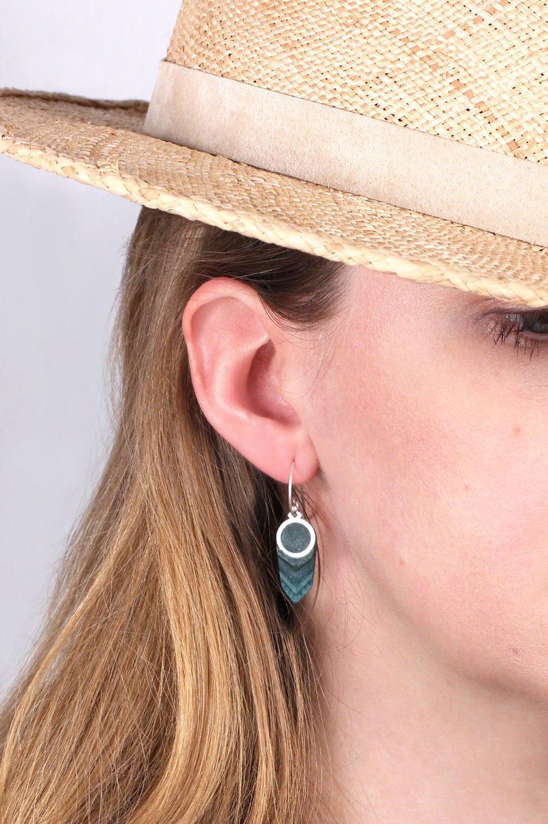 model wearing Panache earrings handmade with forest green resin and hypoallergenic stainless steel