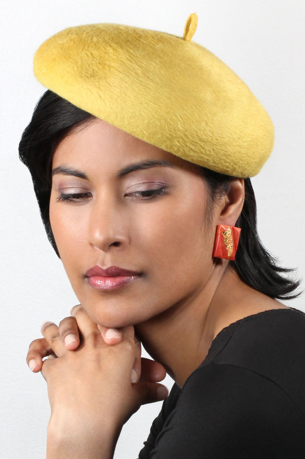 model wearing Bijoux Pépine's coral red and gold leaf Parfait studs
