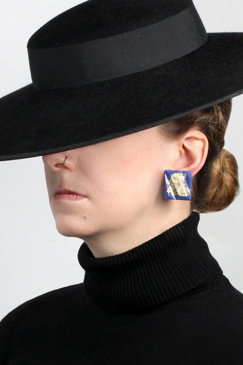 model wearing Bijoux Pépine's classic blue and gold leaf Parfait studs