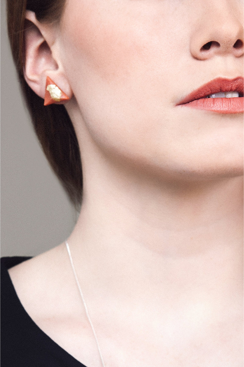 fashion model wearing Bijoux Pépine's hypoallergenic Pyramide studs in coral red