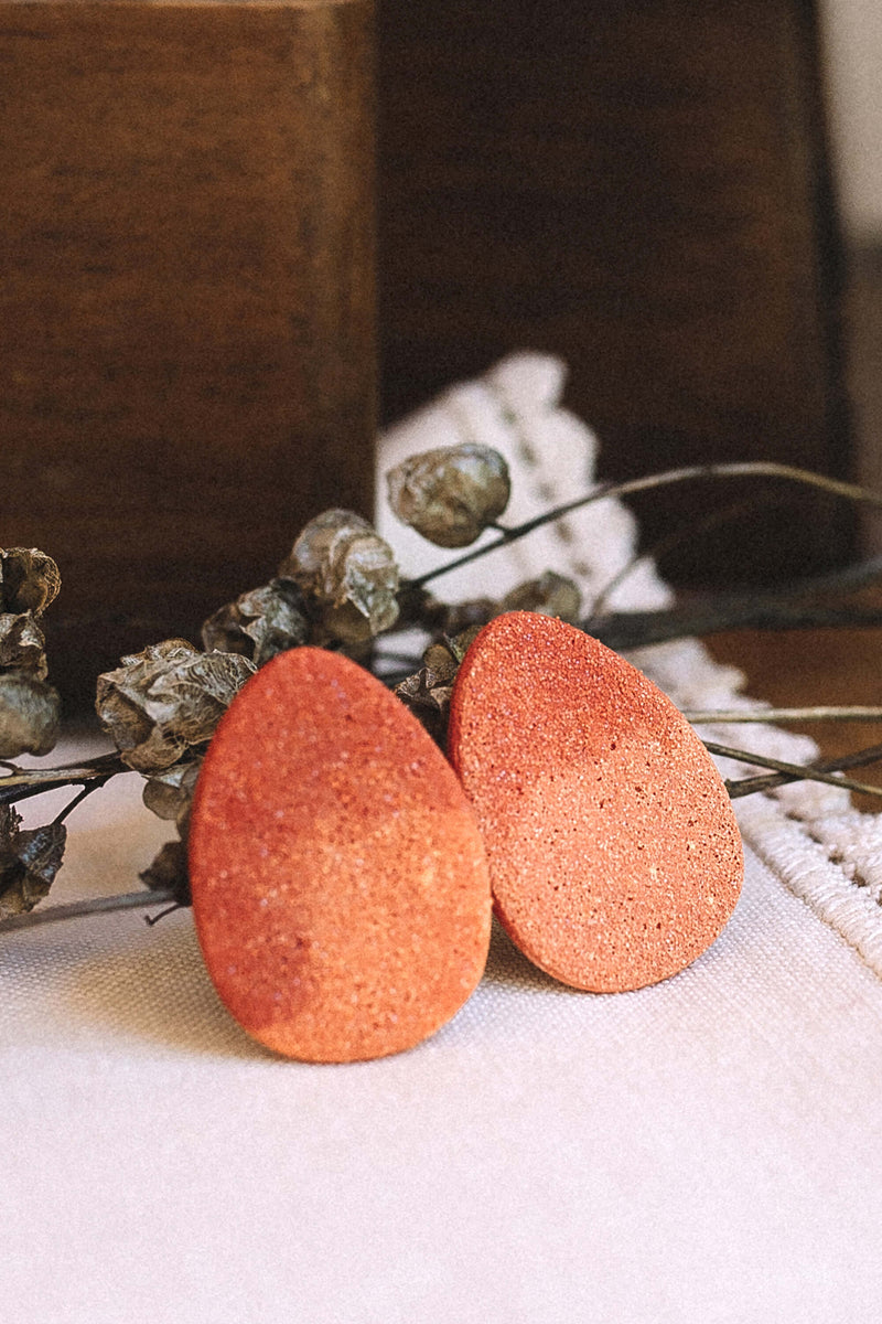 contemporary fashion still life of Bijoux Pépine's Sangatte studs in coral red