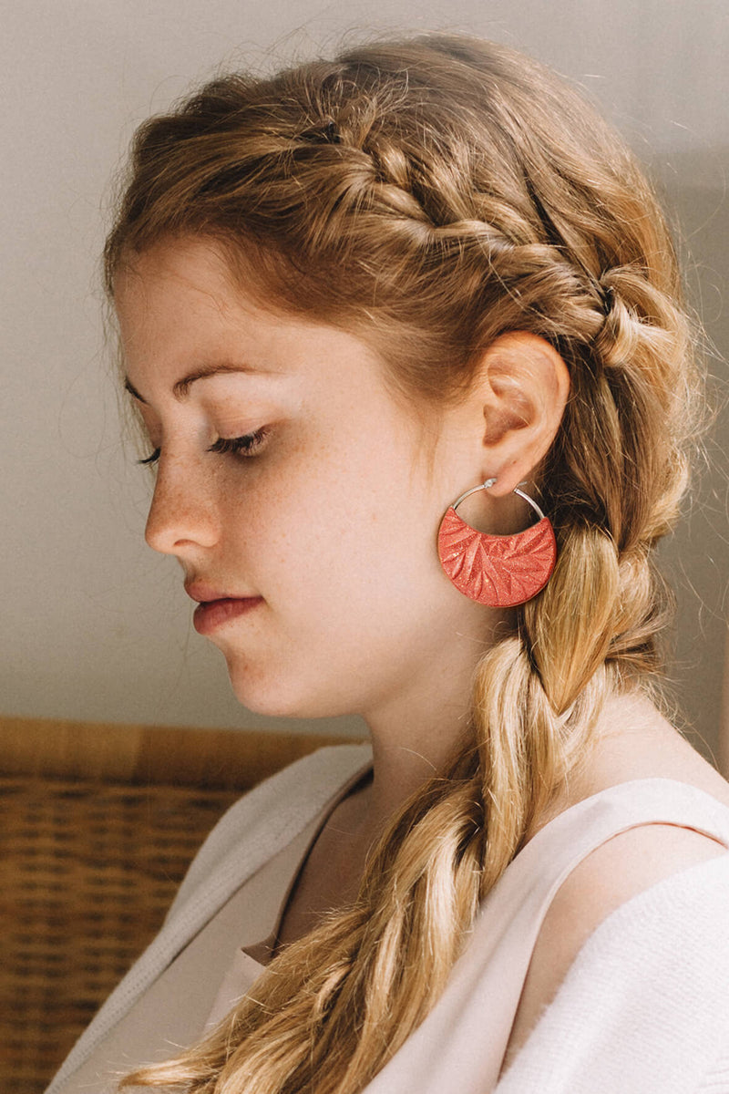 fashion model wearing Séléné earrings, Bijoux Pépine's hypoallergenic luxury hoops in coral red