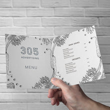 Load image into Gallery viewer, Printed Menu on paper, half folded, held open by customer's hand.