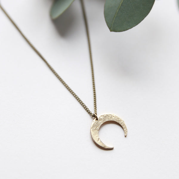 Delicate brass crescent moon necklace handmade by jewelry designers, Cival Collective.