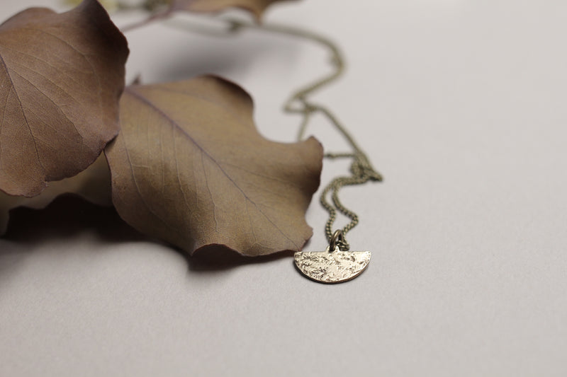Delicate brass moon necklace handmade by Cival Collective.