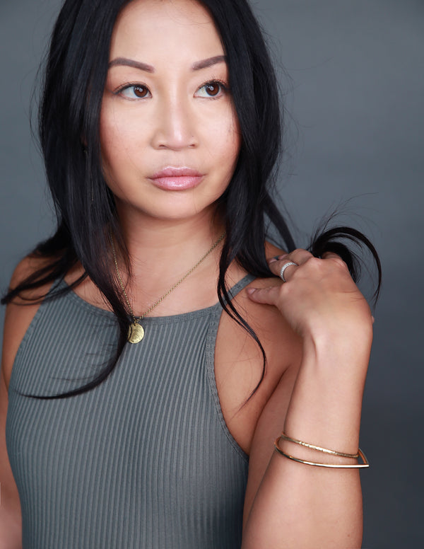 Model wearing handmade brass jewelry by designers Cival Collective.