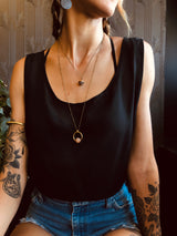 "Model in black tank top wearing an 18 inch ""Coco"" brass cap necklace layered with a longer ""Hazel"" brass suspension necklace."