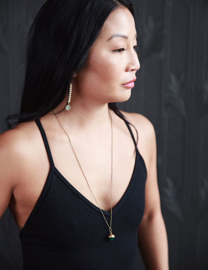 "Model wearing feather chain earrings and ""Coco"" brass capped stone necklace by CIVAL Collective."