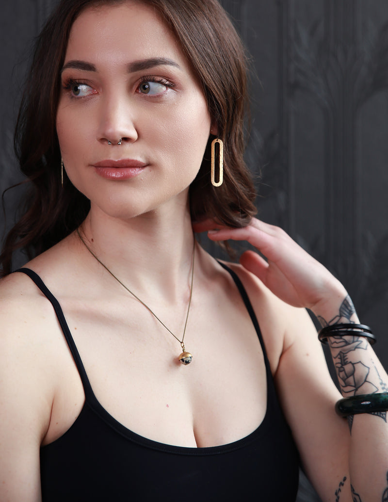 "Model wearing ""Ren"" open oval brass earrings and 18 inch ""Coco"" necklace that has a small Dalmatian jasper round stone half covered in a brass cap."