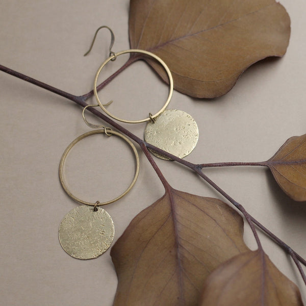 "Close up of ""Corrine"" earrings that consist of an open brass ring on ear wire and a smaller solid textured brass circle hanging below the open ring."
