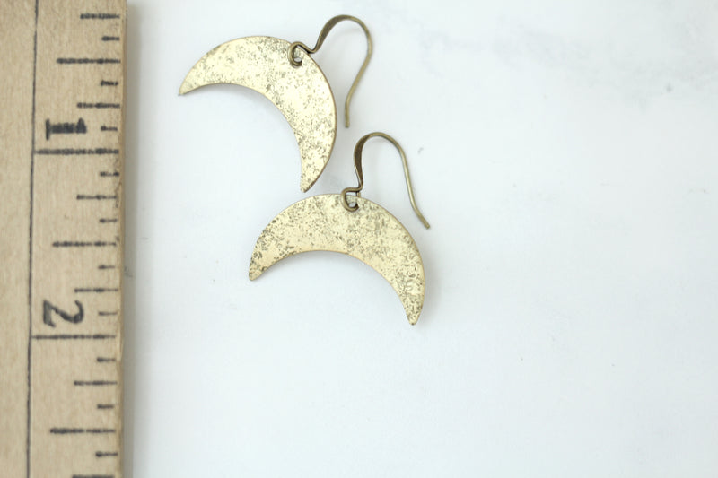 Textured brass crescent moon earrings measuring 1 inch in width and displayed by ruler for reference.