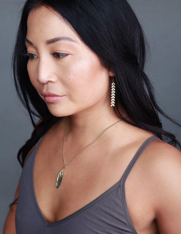 Model wearing handmade feather chain earrings made by designers Cival Collective.