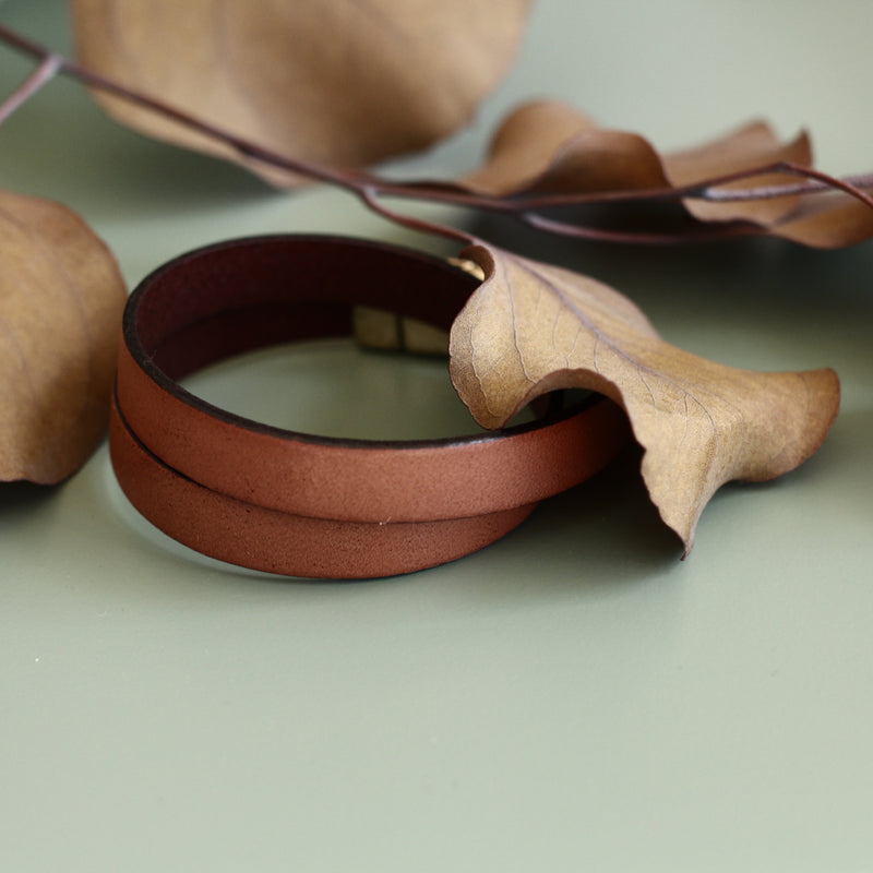 """Acer"" 10mm wide leather double wrap bracelet in tan and displayed on it's side with brown leaves."
