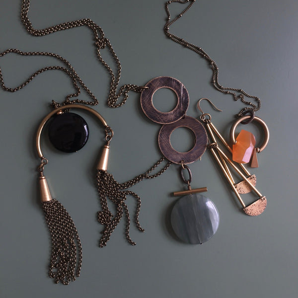 Grouping of CIVAL Collective jewelry including three necklaces with golden sheen obsidian, jade, and carnelian stones and a pair of brass textured earrings.