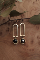 Flat lay shot of brass open arch earrings with faceted smokey quartz rounds set into brass rings & wire wrapped below the archs.
