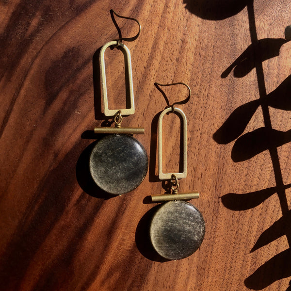 """Elise"" statement earrings that have an open brass arch window, brass bar, and a gold sheen obsidian stone coin all stacked and hanging from a french ear wire."