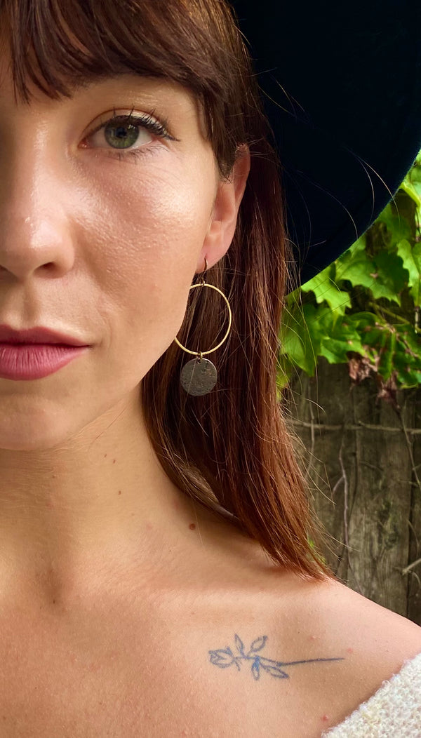 "Model wearing CIVAL Collective ""Corrine"" earrings that consist of an open large ring on ear wire and a small textured solid brass circle hanging on the open ring."