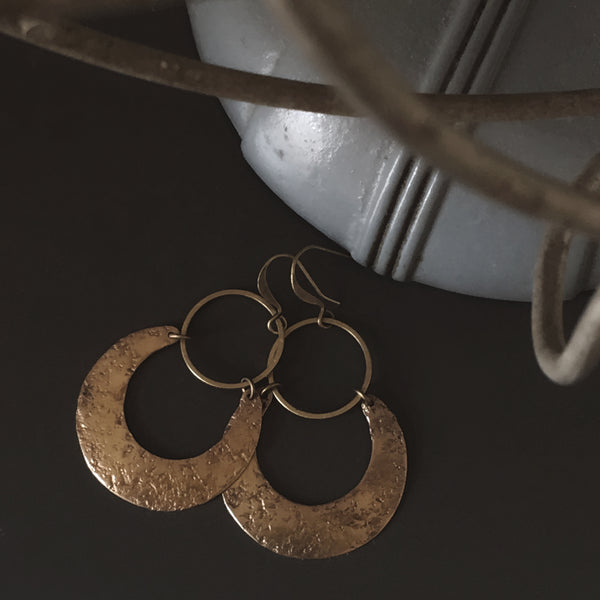 Close up of hand textured brass crescent moon & open brass circle earrings from CIVAL Collective.