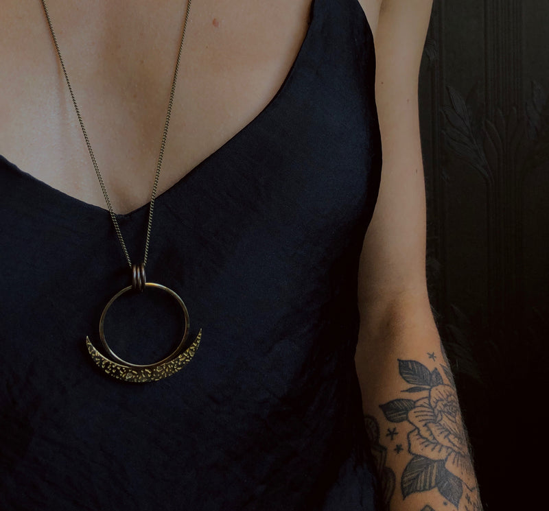 Model wearing a long CIVAL Collective cast necklace that has a large brass ring and attached to the bottom is a textured crescent moon blade.