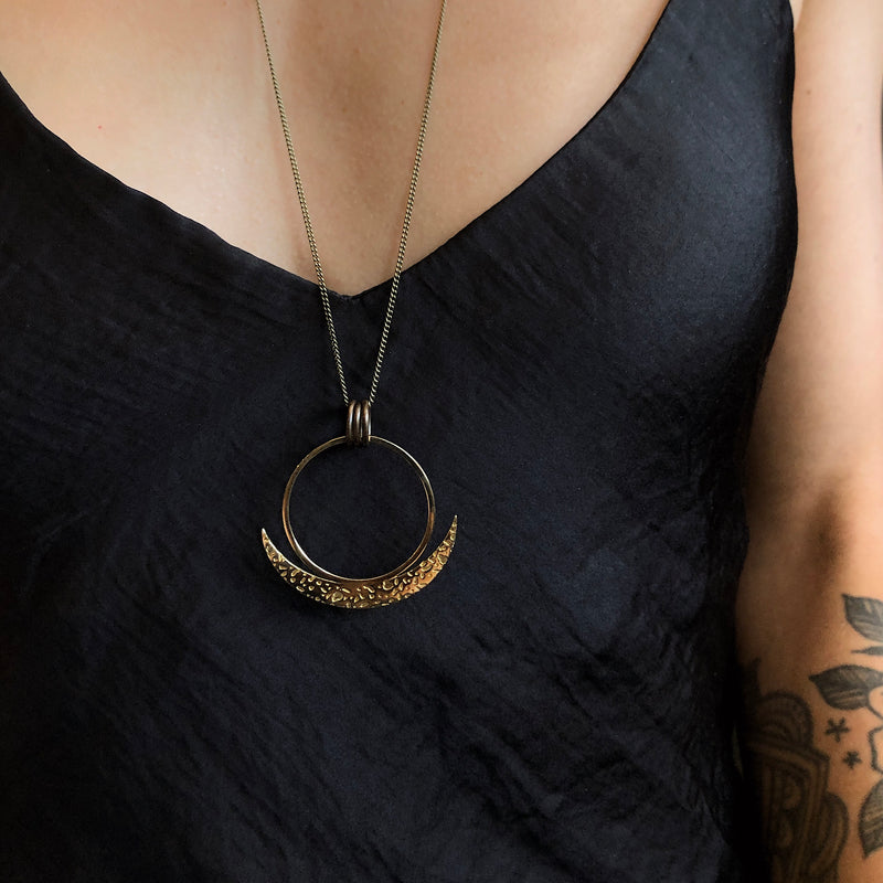 Model wearing a black silk tank top &  long cast necklace, the necklace pendant has a large brass ring with textured crescent moon blade cradling it from below.